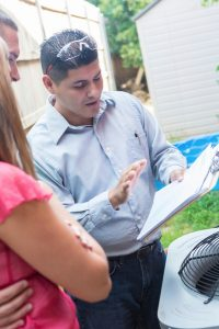 male technician looking over paperwork with female homeowner
