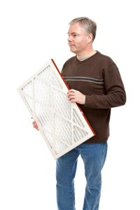 man carrying air filter to put in HVAC system