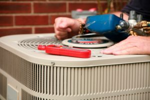 technician's hands working on outdoor ac unit